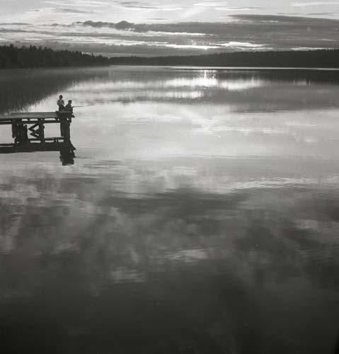 En sommarkväll 1952 sitter två pojkar på en brygga vid Skidtjärn i Bollnäs. Tjärnen speglar himlen med moln och solstrimmor. Längs horisonten skymtar skogen fram med trädtoppar som försöker svälja den sista kvällssolen.