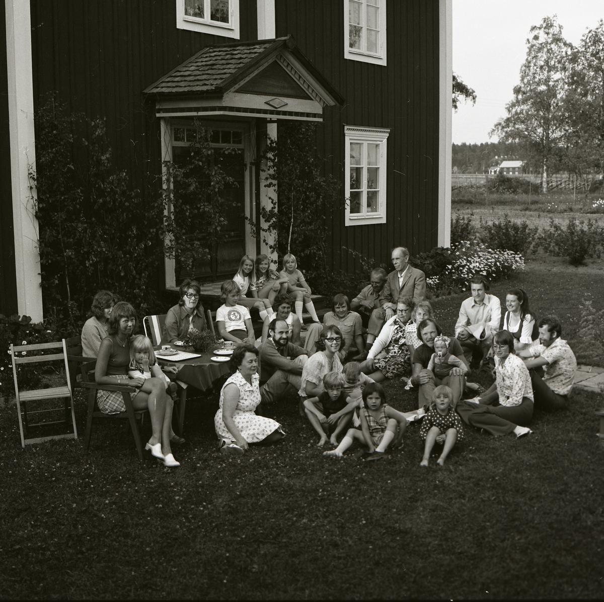 Framför den lövklädda brokvisten har sällskapet samlats för fotografering midsommardagen 1974. Några har slagit sig ned på gräsmattan medan andra sitter på trädgårdsmöblerna och hustrappan. Hela skaran är festklädda i klänningar och fina skjortor dagen till ära.