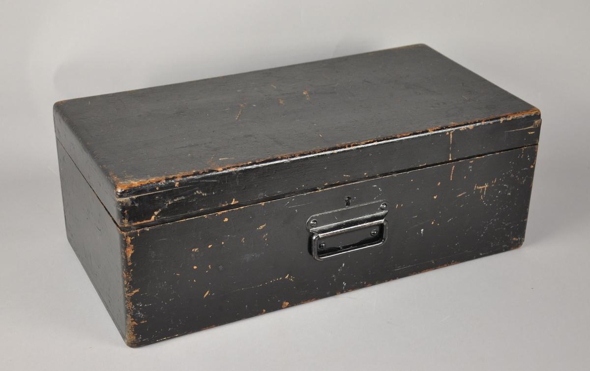 Mørkt skrin med hengslet håndtak. Lokk er hengslet, og skrinet er malt svart på innsiden og utsiden. Nøkkelhull over håndtak, men ingen nøkkel følger med.