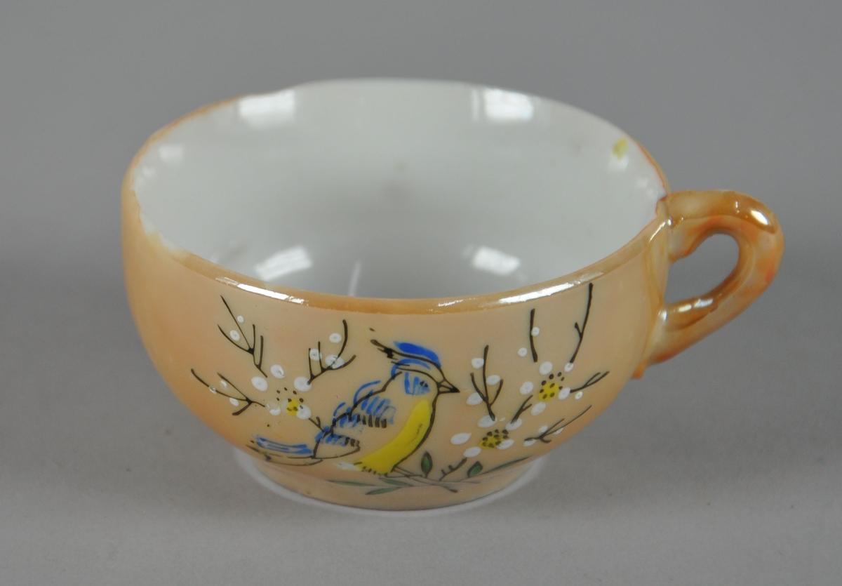 Liten kopp med malt dekor. Koppen har én hank, og utsiden er gullfarget. Malt dekor med motiv av fugl i tre.