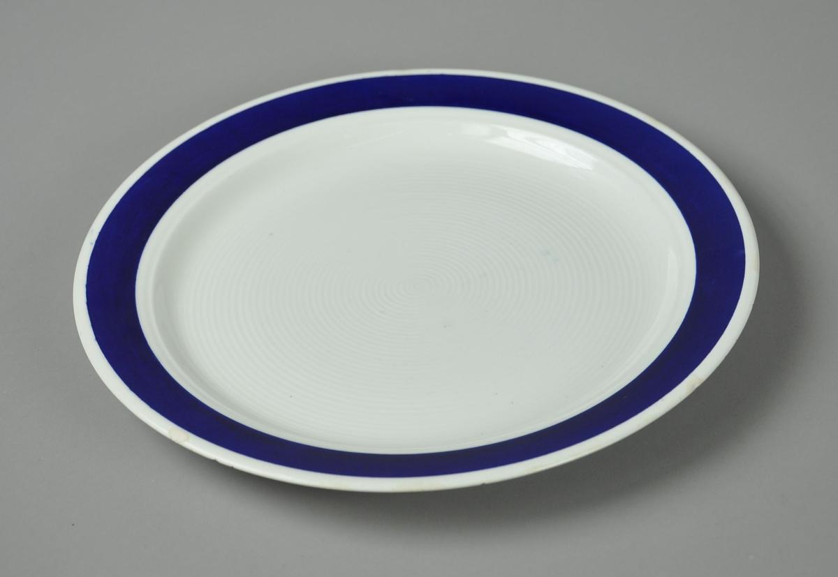 Tallerken av glassert keramikk, med mørkeblå borde påmalt langs kanten. Tallerkenen har konsentriske riller på midten.