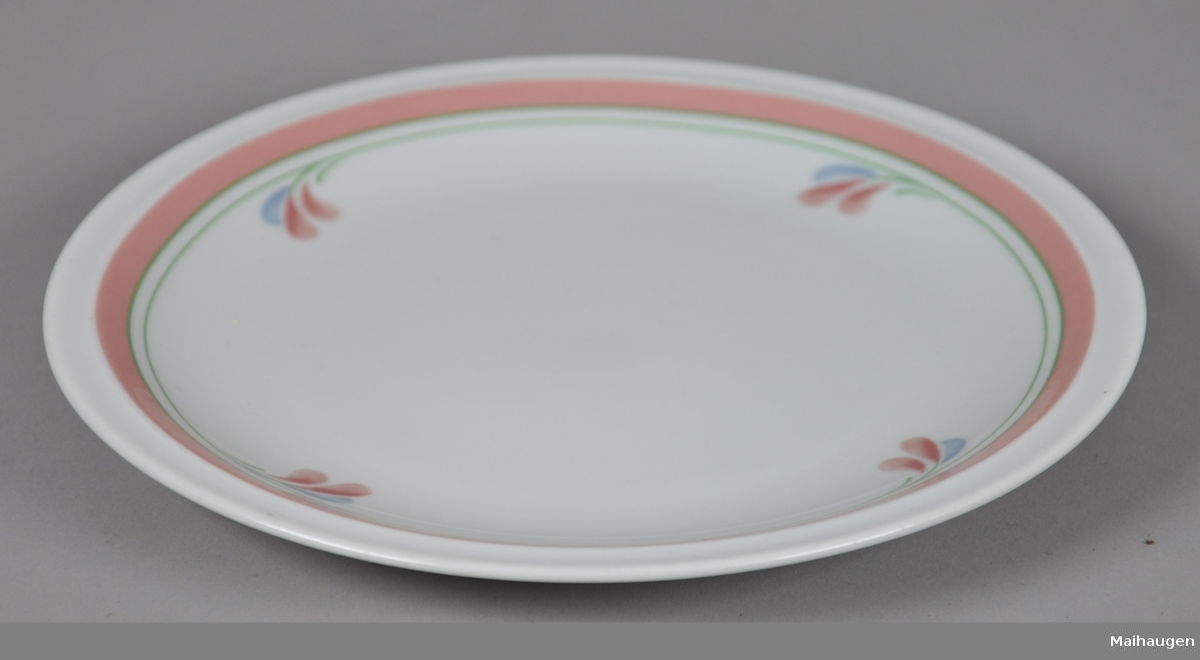 Asjett av glassert keramikk. Asjetten har malt dekor på oversiden, med motiv av linjer og blader som går rundt kanten.