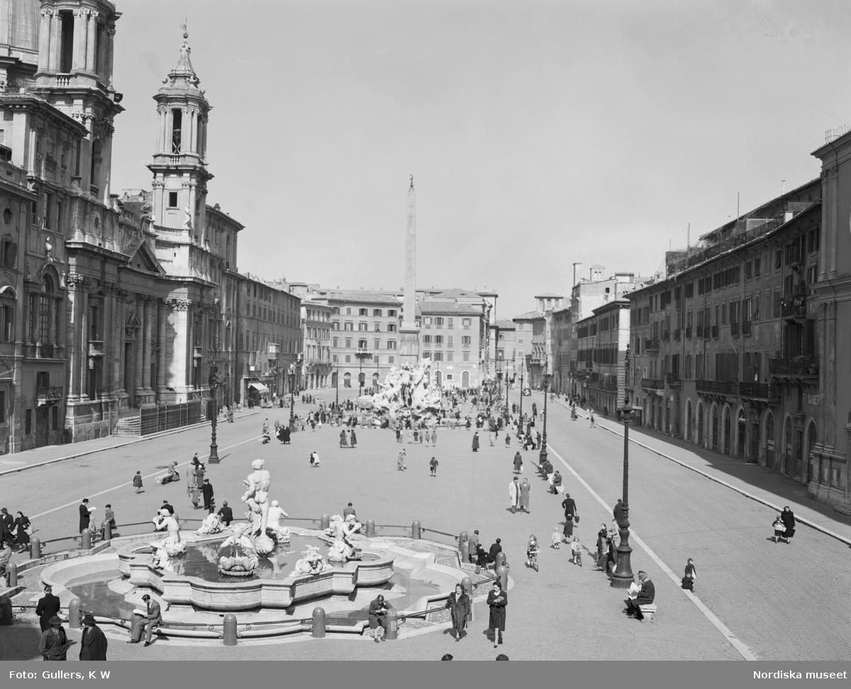 Torg med obelisk, fontän och gamla byggnader.
