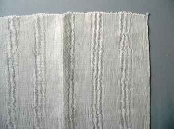 Detta är ett vävprov med vitt bomullsgarn i varp och blekt lingarn i inslag. Ränderna bildas med 3 cm tuskaft och 2,5 cm stramalj. Dubbletter finns.