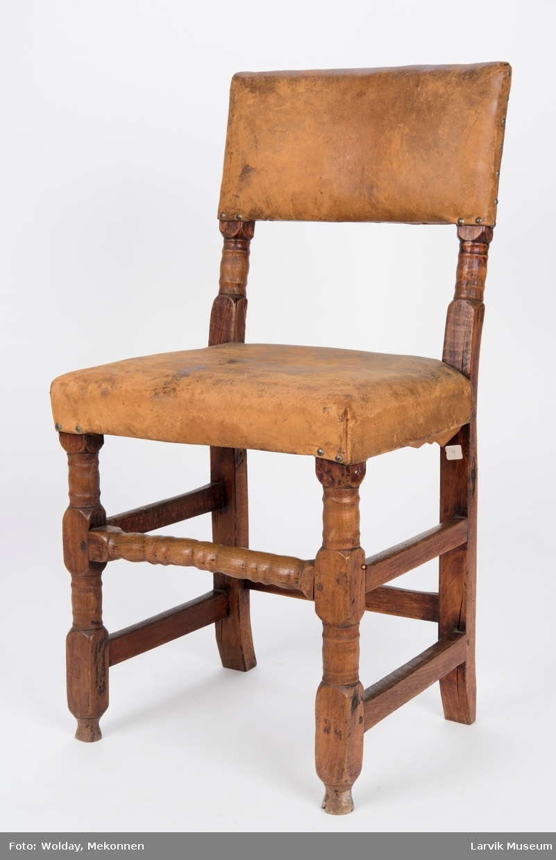 Form: rett avskåret,rekt. rygg, bakstolper i ett med.. Uten armlener.  firesidige bakben, høvlet og dreiet sprosseverk, festet med trenagler,skinntrekk på sete og rygg,festet med messingstifter