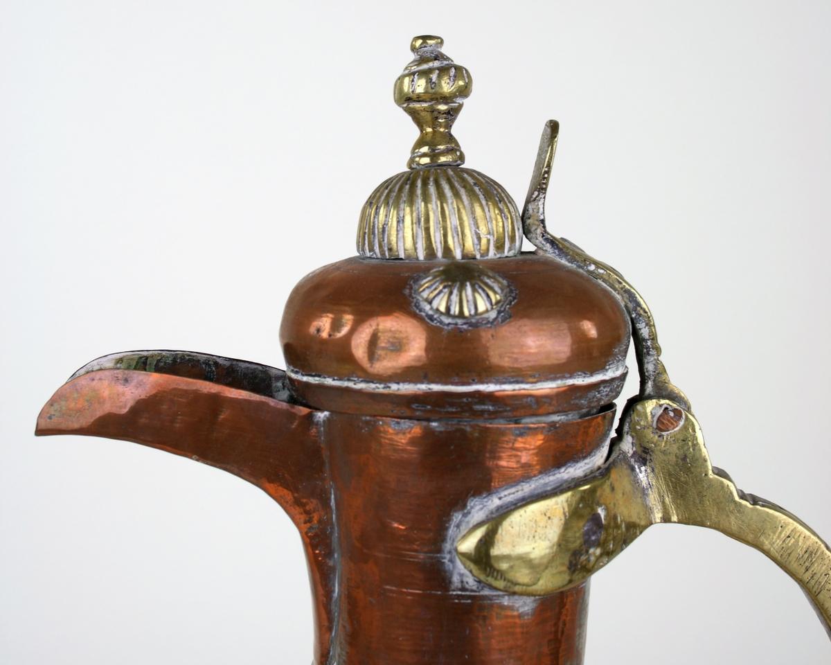 Kanna av vitmetall och mässing med en koppar yta. Kopparytan bortnött på vissa ställen och visar metallen under. Lock och pip. Svängd form. Handtag av mässing. Egyptisk. Troligtvis använd till vatten.