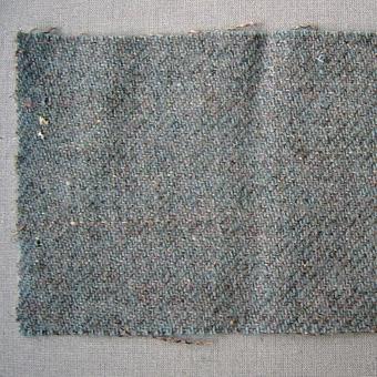 Vävprov, blågrå-melerat ylletyg vävt i liksidig kypertbindning. Tyget är valkat. Varp i blått 1-trådigt ullgarn.Inslag i grått 1-trådigt ullgarn.