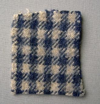 Vävprov, rutigt ylletyg vävt i liksidig kypertbindning. Rutigt i blått och naturvitt, 5 x 5 mm stora rutor. Tyget är valkat. Varp och inslag i blått och naturvitt 2-trådigt ullgarn.