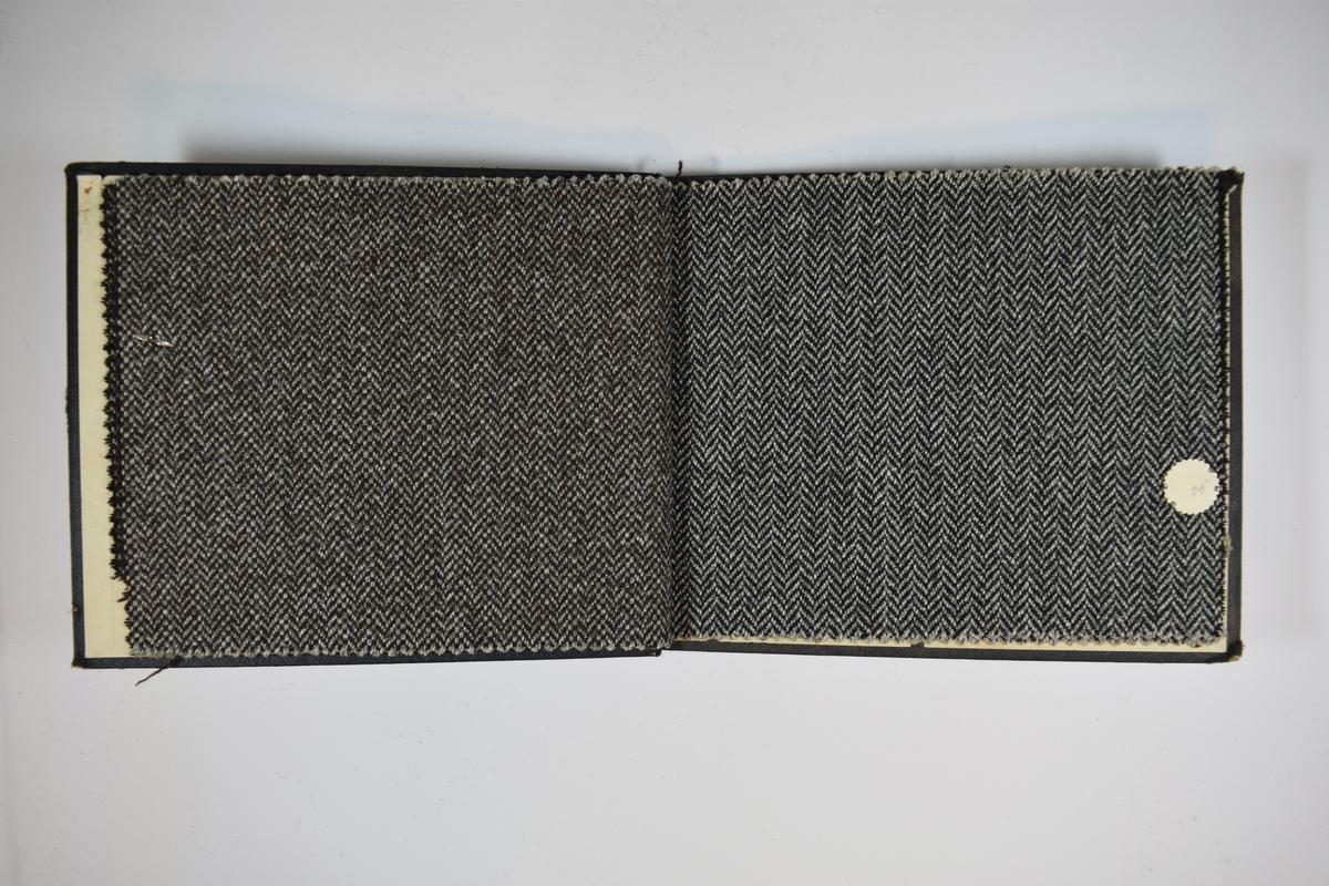 Prøvebok med 4 stoffprøver. Middels tykke stoff med fiskebensmønster eller lignende. Stoffene er merket med en rund papirlapp, festet til stoffet med metallstifter, hvor nummer er påført for hånd. Innskriften på innsiden av forsideomslaget indikerer at alle stoffene har kvaliteten 175B.   Stoff nr.: 175B/33, 175B/34, 175B/35, 175B/36.