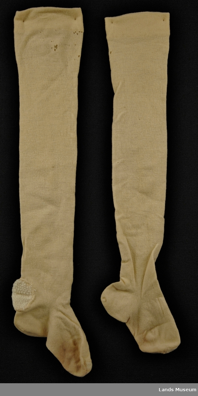 Tricotageprodukt. Glattstrikket. Dobbel kant øverst. Timeglasshæl og flat tåfelling. Strømpene har vridd seg, antakelig p.g.a. for hardt tvinnet garn i forhold til masketetthet.