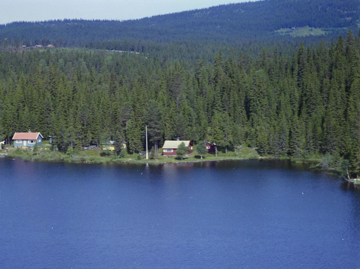 Nord Mesna. Den røde hytta er Olaus Nilsengs hytte. Den blå hytta er Gudbrandsens hytte, vann, vatn, innsjø, skog, bygninger, hytter,
