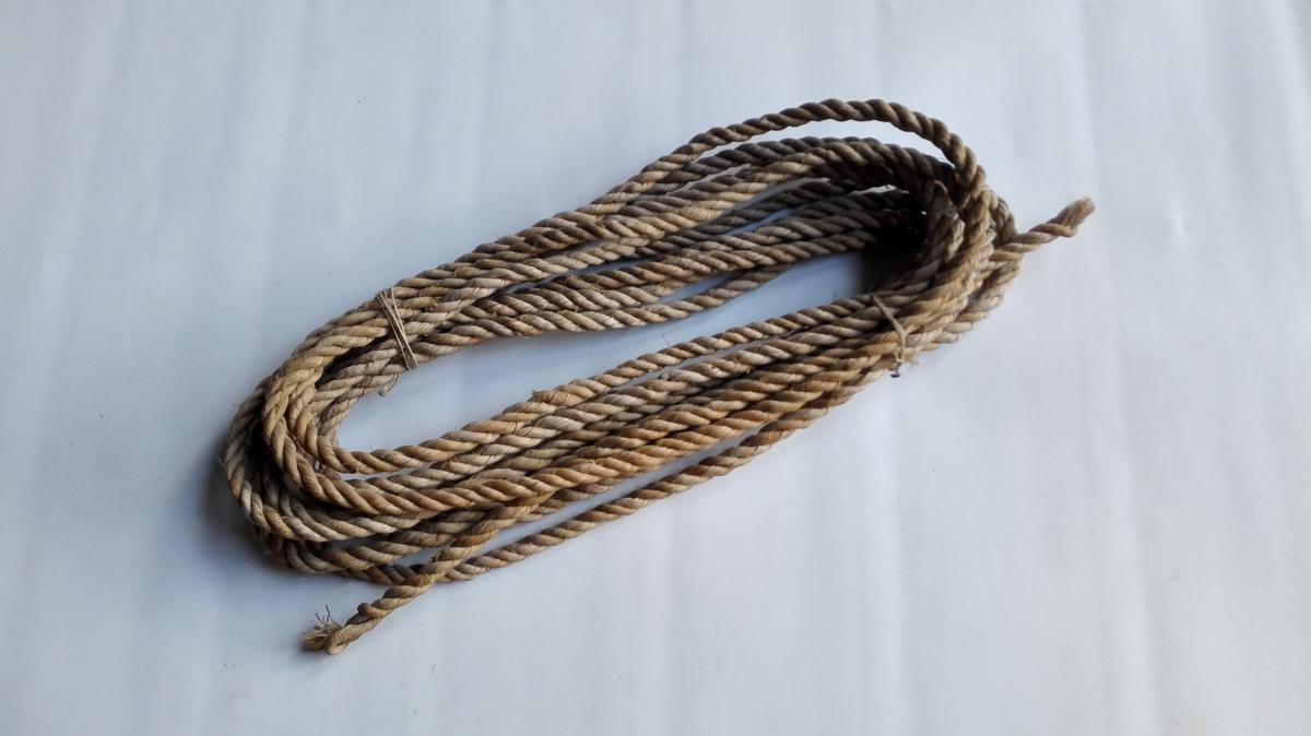 """Bastetaugarbeide.  Bastetaugarbeide visende fremstillingen av bastetaug fra barken flækkes av lindetræet til tauget er færdig i fölgende serier (12284 - 87): 12287 - Et ferdig spundet og tvinnet bastetaug 9,20 m langt. I Balestrand herred, særlig Fjærland og Vetlefjorden lager man fremdeles bastetaug til eget bruk. Av redskaper til spinning av basten brukes en saakaldt """"kegle"""", der kan være enkelt og dobbelt. Begge sorter has i museet. Nærværende er sendt museet av en gammel mand i Vetlefjorden, der har drevet med bastetauglagning.  Gave fra Tomas Feten, Vetlefjorden."""