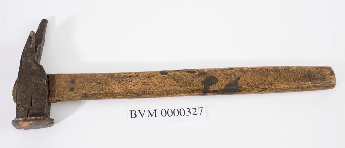 """NTM: """"Fra snekkerverkst. loft i Kongsberg. Er gjordt ved Sølvverket."""" Trolig brukt ved lekting av for eks. tak. De to """"hakene"""" bak på hammeren har ulik lengde. Dvs. at man kunne trekke ut spiker som en vanlig hammer, samt at en lett kunne ta opp igjen lekter som låg feil."""