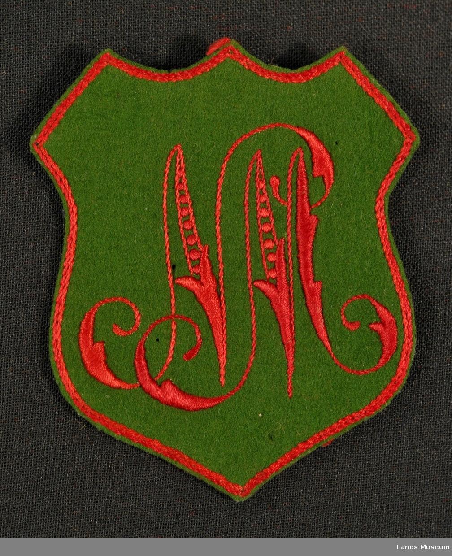 Navemerke til innsying på kleplagg. Grønn filt med rødt broderi. Kant brodert i rødt med kjedesting rundt merket.