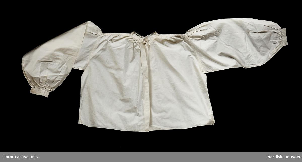 """Huvudliggaren: """"Kvinnodräkt fr. Kåkinds hd, Västergötland."""" En hel rekonstruerad folkdräkt som bär spår av skärningen på 1890-talets modedräkt. Har tillhört frk. Lilli Zickerman, grundaren av Föreningen för Svensk Hemslöjd 1899. Hon kom från Skövde. a) Liv av hemvävt ylle, rött med konstvävda ränder i grönt, mörkrött och blått. b) Överdel av vitt bomullstyg. c) Kjol av randigt bomullstyg vitt, rött, brunt och grönt. d) Förkläde av rött och vitt randigt bomullstyg. e) Huvudduk, bomull, blå, röd och vitrutig.  Såsom huvudbonad till dräkten hör bindmössa.""""  a. Livstycke, rekonstruerat efter äldre förlaga sannolikt. Av halvylle, vit bomullsvarp, inslag botten i ripsbindning med rött ullgarn samt ränder i tvåskyttling med vinrött, svart samt 2 nyanser grönt ullgarn."""