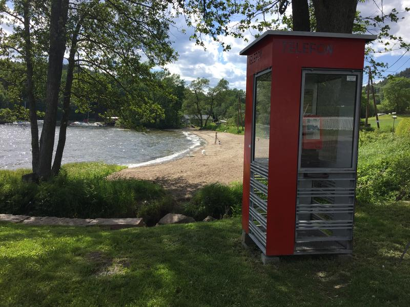 Rød telefonkiosk ved badestrand i Hyggen