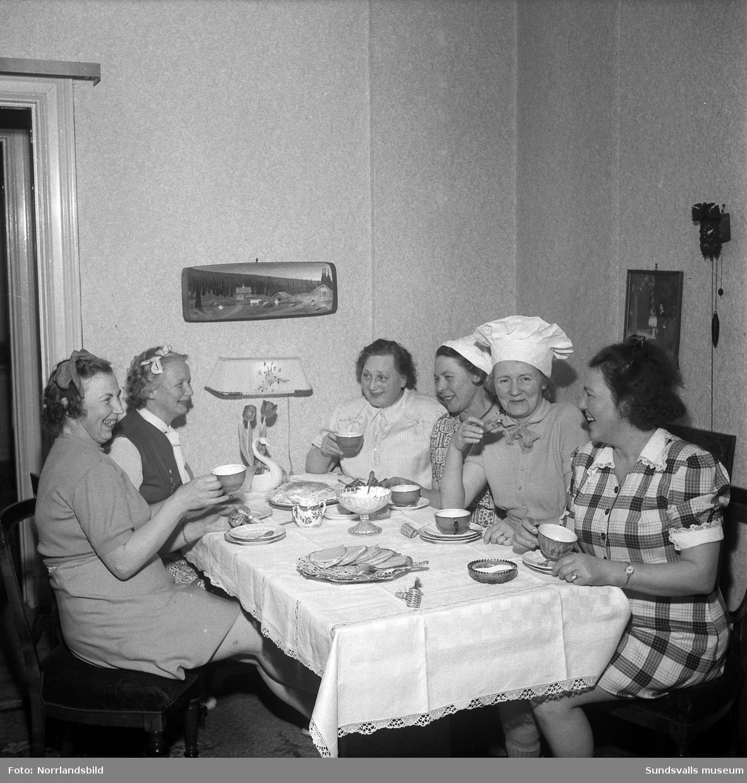 Humoristisk julgransplundring med sex glada damer i en syjunta (Fredriksson). En av kvinnorna spelar dragspel.