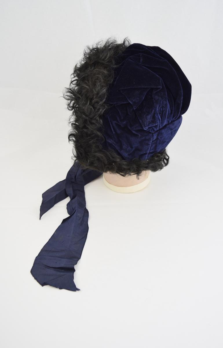 Lue i velour lagt i folder i nakken og over pullen. Femkantet stykke i nakken. Sort pelskant og knytebånd under haken. Foret med sort glatt stoff på innsiden.