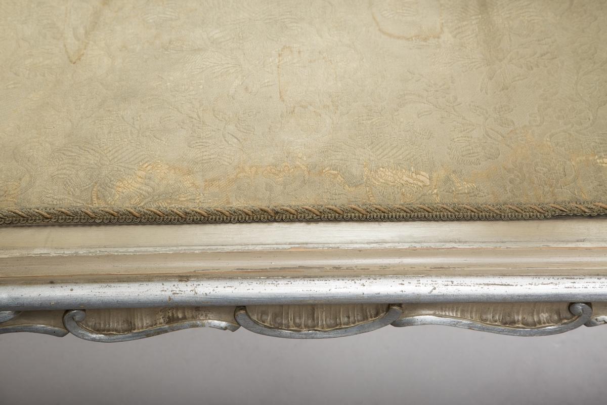 Vitrineskap i nyrokokko. Front og sider i glass, bakveggen av tre, på innsiden dekket av blyinnfattet speil. Sideveggene har buet glass. Alt treverk rikt utskåret. Malt lysegrått med forsølvete ornamenter. 3 hyller trukket med stoff, 1 dør. 4 cabriolebein med voluttavslutning. Øverste profilerte gesims med stort, utskåret toppstykke hvor to speil er innfelt.
