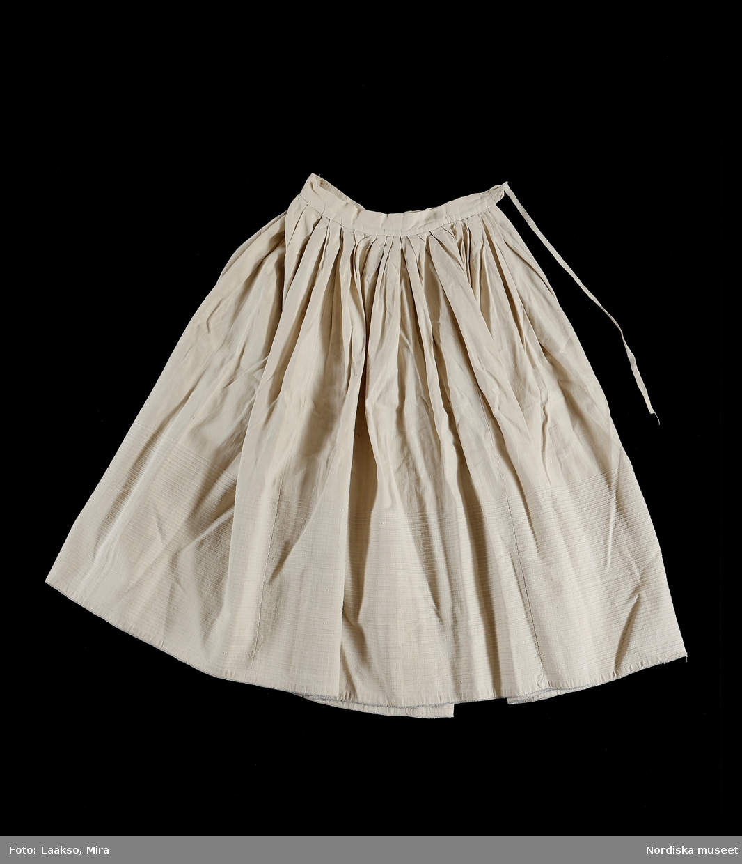 Underkjol av vit hemvävd halvlinnelärft där de nedersta 30 cm på kjolen har en invävd grövre bomullstråd på varje cm för att få bättre stadga och hålla ut kjolen.  Sydd av 5 våder,  3 cm breda veck runt livet och 4 cm bred midjelinning, sprund i en söm, linningen knyts med  långa hemvävda bomullsband. nederkanten skodd med  en tunn flätad bomullssnodd i blått och vitt för att förhindra slitage. Kjolen helt handsydd. Har tillhört givarens farmor Maja-Stina Svensson gift med riksdagsmannen Anders Svensson i Bosgården. /Berit Eldvik 2010-09-23