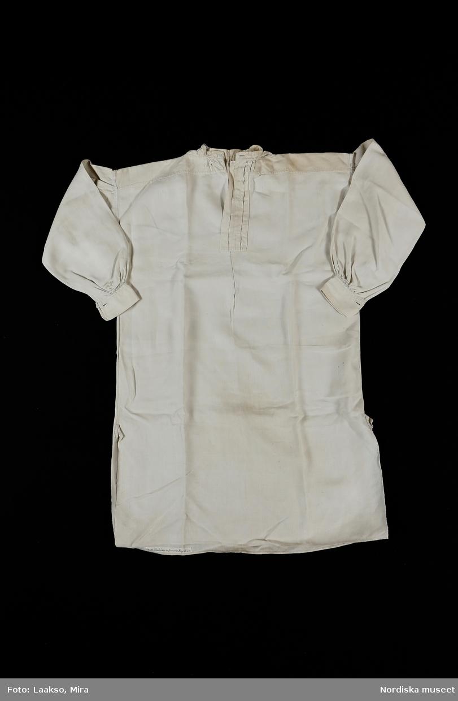 Mansskjorta av vit handvävd linnelärft, ett bålstycke, sprund i sidorna 31 cm långa med steglapp. Axelok med halsspjäll. Ståndkrage 2 cm och 7 cm brett förslag båda av halvlinne och knäppta med vit porslinsknapp. Vidsydd ärm med ärmspjäll i ett med ärmen och 4 lagda veck på kullen. Rynkad mot bred ärmlinning knäppt med 1 knapp och knapphål. Fina efterstygnssömmar på ärmlinningen och små nuggor i kanten. Helt handsydd. Antagligen sydd av Per Larssons hustru, de gifte sig på 1850-talet och bodde på ett torpställe under Näsbyholms gård. Jfr äldre skjortor från Vemmenhög t.ex. 5948 daterad 1801 och 5953 daterad 1843, som representerar 2 tidigare stadier i skjortans utveckling. /Berit Eldvik 2010-06-01