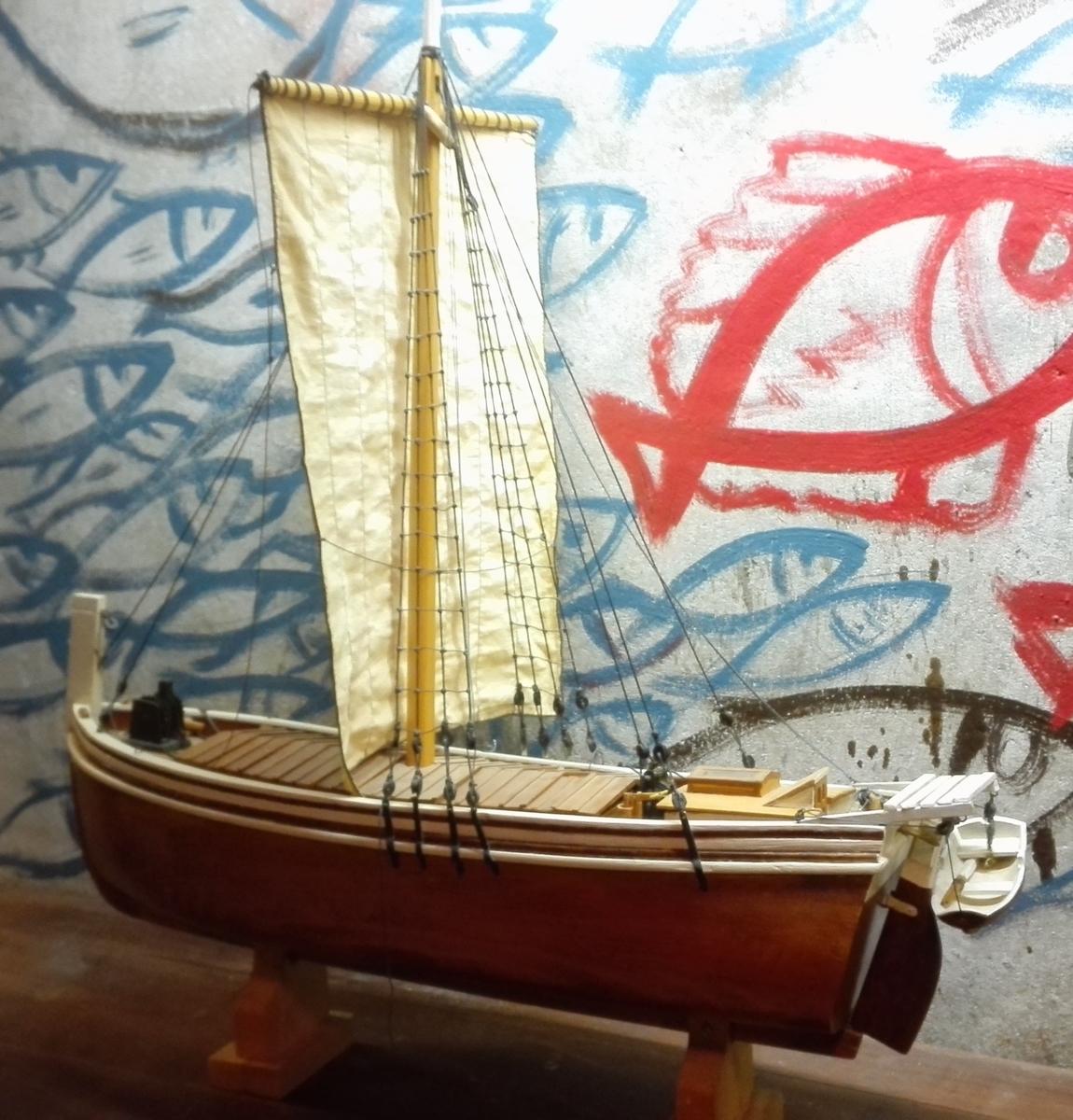 """Forseggjort og detaljrik modell av  jekta """"Sygna"""". Skroget utskore av eit heilt trestykke. Dekk og lasteluke av tynnt tre. Tretak med glasvindauge over kahytt. Kahytten innreidd med bord, og stolar, seng og komfyr. Rigga med  råsegl, og med lettbåt med årar på hekken. Treror og rorkult,  jektepumpe, anker med ankerspel.   I toppen av seglet, blå vimpel med tekst SYGNA"""