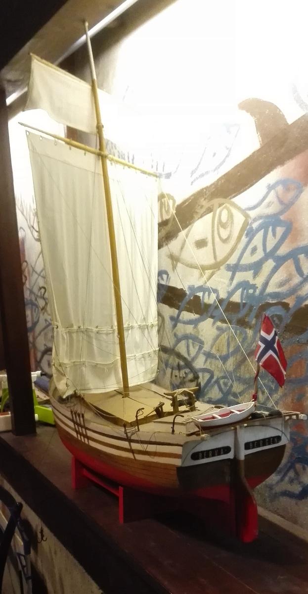 """Ein  forseggjort og detaljert modell av av jekta """"Berva"""". Skroget er utforma og uthola av eit heilt trestykke. Dekk med lasteluker av av finer. Modelljekta er rigga med råsegl. Ho har ror og rorult i tre, stiliisert jektepumpe, hekk med lettbåt, flaggsstong med norsk flagg, ankerkjetting og anker.   På bakspegelen er tekst: BERVA  BERGEN"""