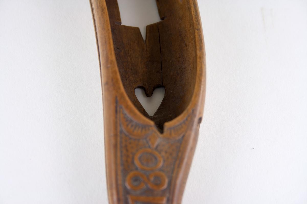 Vävskyttel i trä med skuren dekor. Årtalet 1780 och initialerna CSH på skyttelns ovansida där även en enkel rocaillebård finns. I botten ett utskuret hjärta.