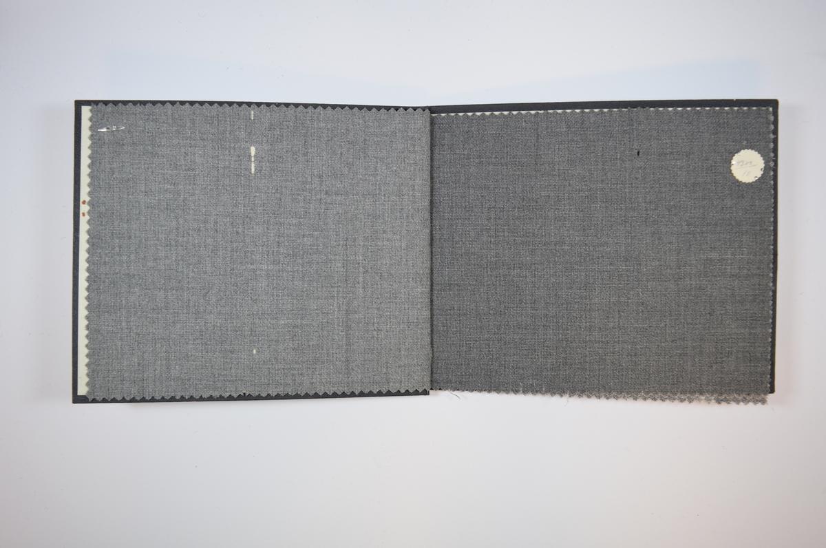 Rektangulær prøvebok med fire stoffprøver og harde permer. Permene er laget av hard kartong og er trukket med sort tynn tekstil. Boken inneholder tynne, men tette, melerte grå stoff. Toskaftbinding. Ingen av stoffene er brettet dobbelt i boken. Alle stoffene er merket med en rund papirlapp, festet til stoffet med metallstifter, hvor nummer er påført for hånd.   Stoff nr.: 4300/9, 4300/10, 4300B/1, 4300B/2.