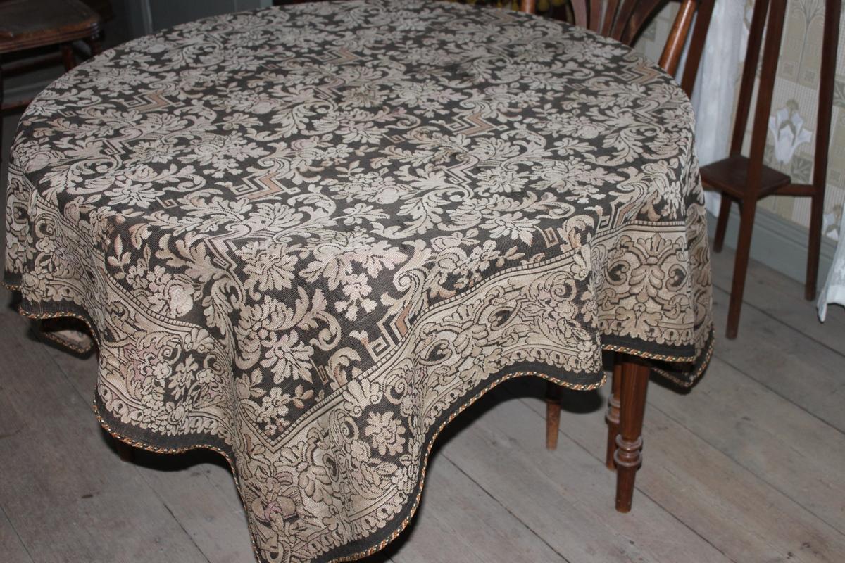 Fyrkantig matsalsbordsduk av grövre typ. Mönstervävd i maskin, med akantusliknande slingor och geometriska mönster, blad och maskaroner i brun, beige och lila. Duken är kantad med en snodd i grönt, brunt och orange.