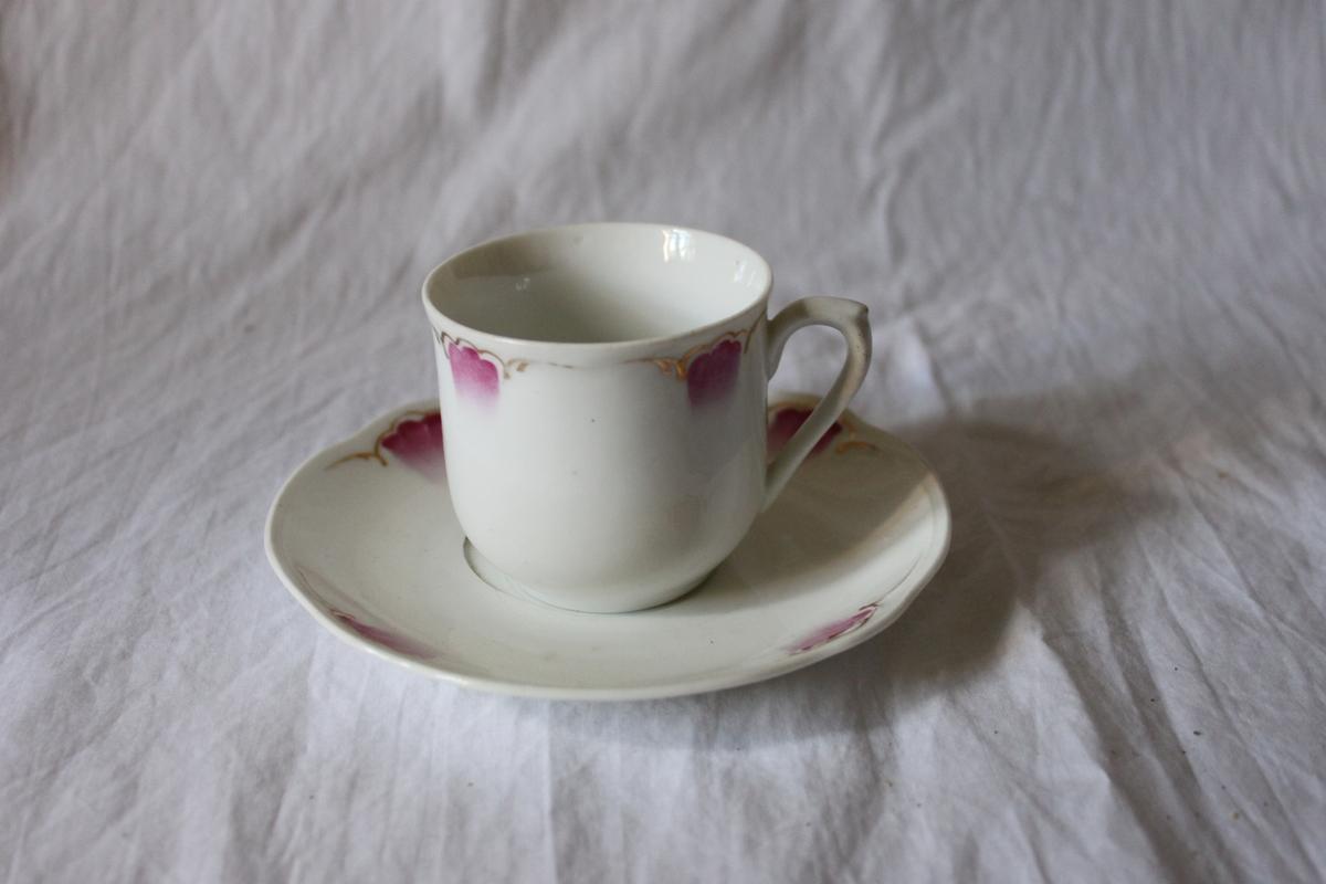 Kaffekopp av porslin, svagt klockformad med lodgrepe. Målad dekor i form av kallrosa, tulpanliknande blomma med guldslinga.