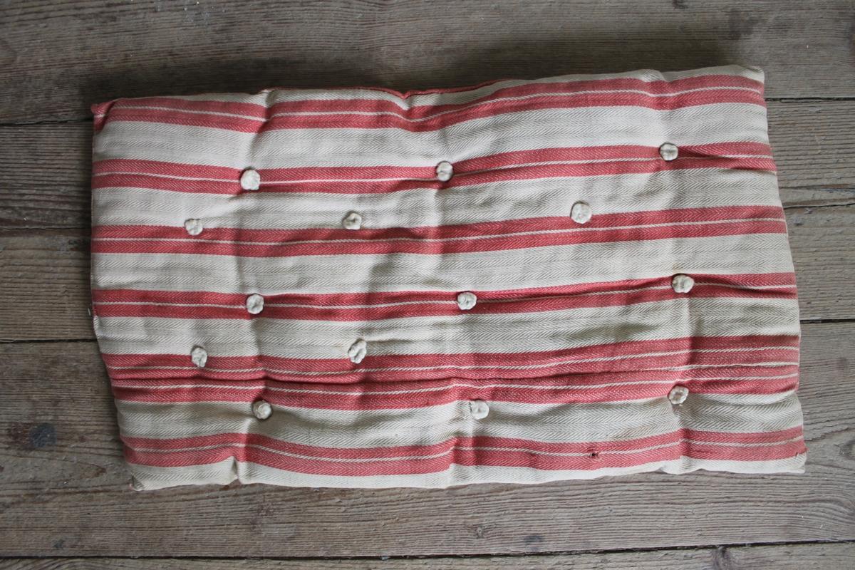 Hemmasydd vit madrass med röda ränder. Tillhör docksäng. Stoppning troligtvis bomull.