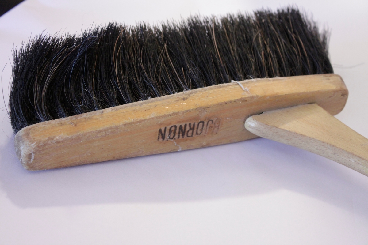 Sopborste med långt handtag i trä med borst av tagel. Borsthuvudet har Björnön inpräglat på ovansidan.