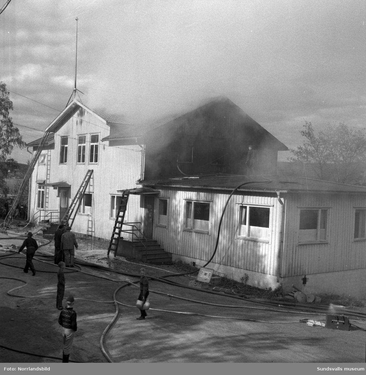 En stor serie bilder från en eldsvåda i kontorsbyggnaden till Luckstaverken, Lucksta ångsåg. Släckningsarbete pågår och massor av människor hjälps åt att rädda så mycket lösöre som möjligt. Elden startade i på övervåningen i kassören Sven Perssons bostadslägenhet. Persson räddade sig ut genom att hoppa från balkongen på baksidan. Brandkårerna från Attmar, Tuna och Sundsvall lyckades till slut få bukt med elden men övervåningen totalskadades och det kafé som fanns inrymt i bottenvåningen fick stora brand- och vattenskador.