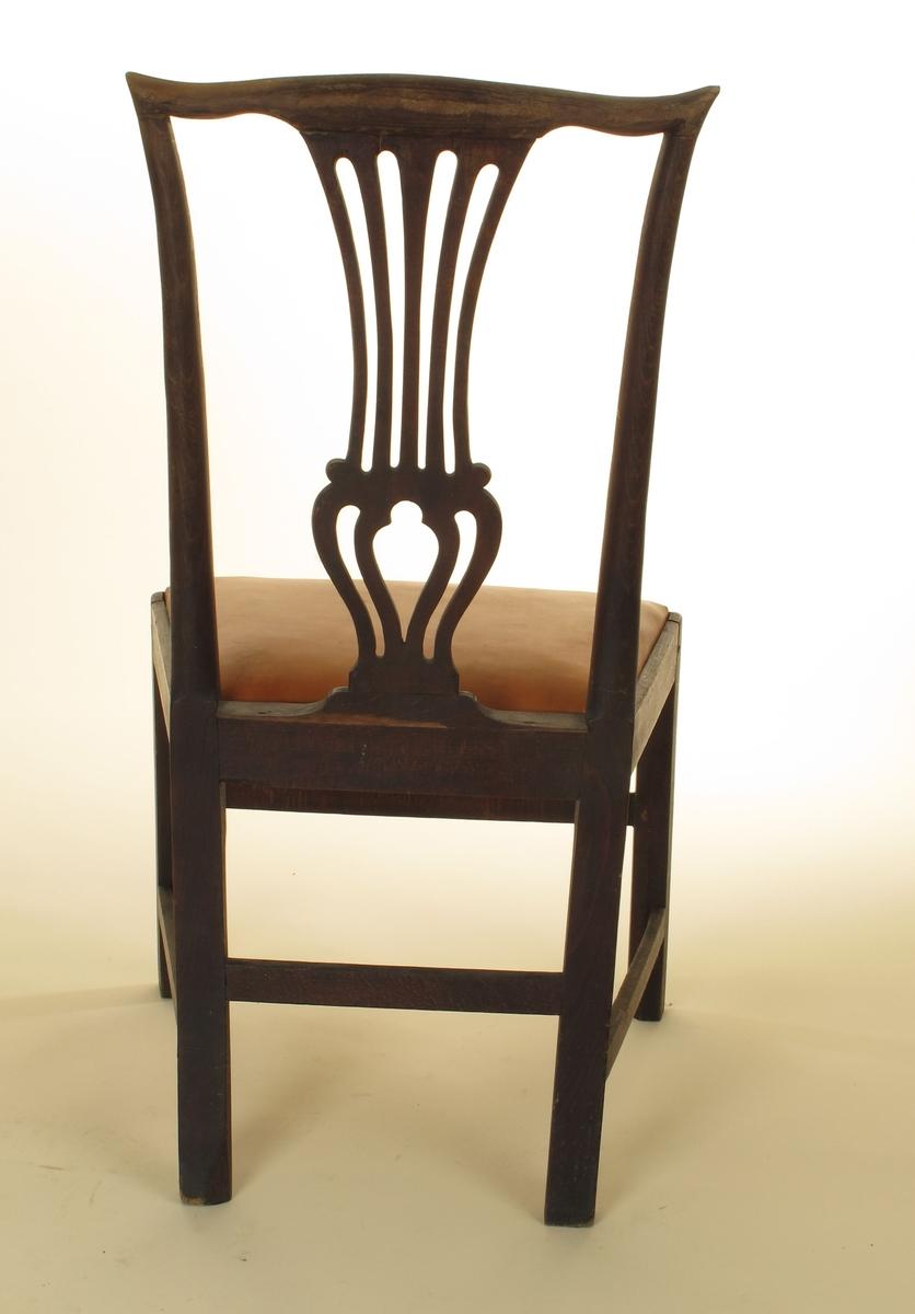 Rette ben med bindeledd mellom, bredt og dypt trapesformet sete. Løst,  stoppet sete trukket med kalveskinn, passer ned i fals i sargen. Svakt svungne skuldre i toppstykket, midtbrett med fire spiler, i nedre del vaseformet. Sprekk i ryggbrettet, th. satt  på et lite rektangulært stykke, festet med  fire små stifter. Sprekk i sargens bak kant Helt løs i sammenføyningene.