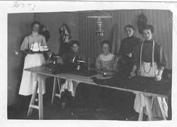 Fem kvinner rundt et bord i ei systue.