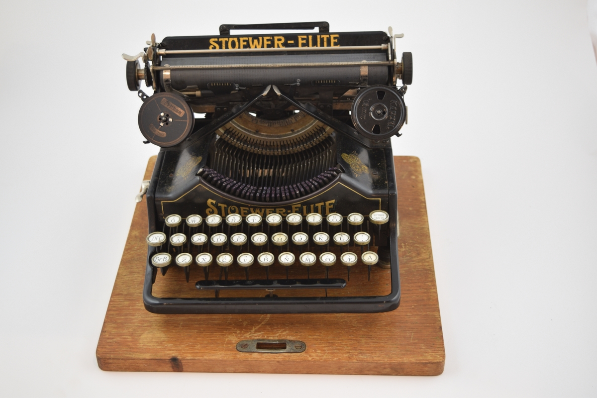 Skrivemaskin i brunbeiset og lakket trekasse med låsbar overdel. Overdel (lokket) er flatt med pultformet skråning i forkant. Håndtak i jern. Svart skrivemaskin med overføringsbilder og logo i gull, Hvite taster.