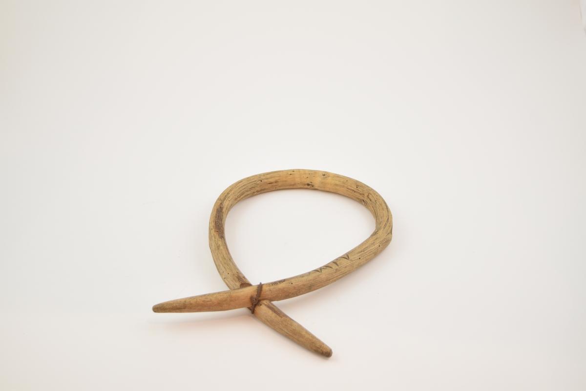 Laget av en hel gren av einer, bøyd i dråpeform og festet ved et utskåret hakk i begge ender med ombundet ståltråd. Inititaler er skåret inn i treet.