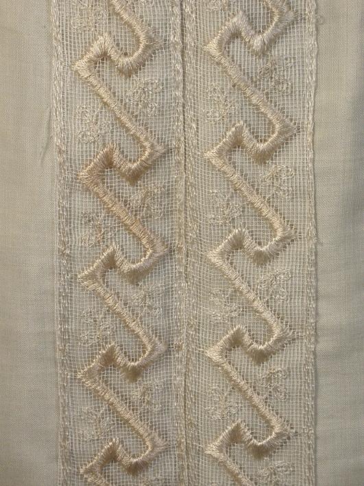 Brudklänning av gulvit yllemuslin bestående av liv, kjol och skärp.  Liv: Helskuret framparti, veckad isättning, påsytt ok kantat med siden. Påsydd och broderad nätspets av silke som går ned till midjan. Knäppes bak med hakar och tränsade hyskor. Ståkrage med 3 st isydda fjädrar, spetsprydd och rysch i överkanten. Lång ensömsärm med lagda veck och rysch i underkanten. Fodrad med vitt bomullstyg. Hänghällor vid fodrets axelsöm. Knäppning mitt bak. Fodret knäppes med 12 st hyskor och hakar växelvis. Livet knäppes med 14 st hakar och tränsade hyskor (inklusive kragen). 1 hake på utsidan ryggen för upphäktning av kjolen. Mycket långa ärmar, sprund som knäppes med 2 st hakar och tränsade hyskor. Mått i cm: Hellängd 47, kraghöjd 7,5, ärm 65.  Kjol: 7 st utställda våder. Fodertyget fastsytt i sömmarna. Knäppes mitt bak med 7 st hyskor och tränsade hakar. Påsydd linning, knäppes med 2 st hyskor och hakar. Påsydd broderad nätspets lodrätt på framvådens mitt. Uppfållad nedtill med 11,5 cm bred snedslå. Litet släp.  Mått i cm: Längd fram 111,  längd bak 113, midjan 71.  Skärp: Av siden. Tvärgående lagda veck. 5 st isydda fjädrar, knäppes med 4 st hyskor och hakar. 71 cm långt.