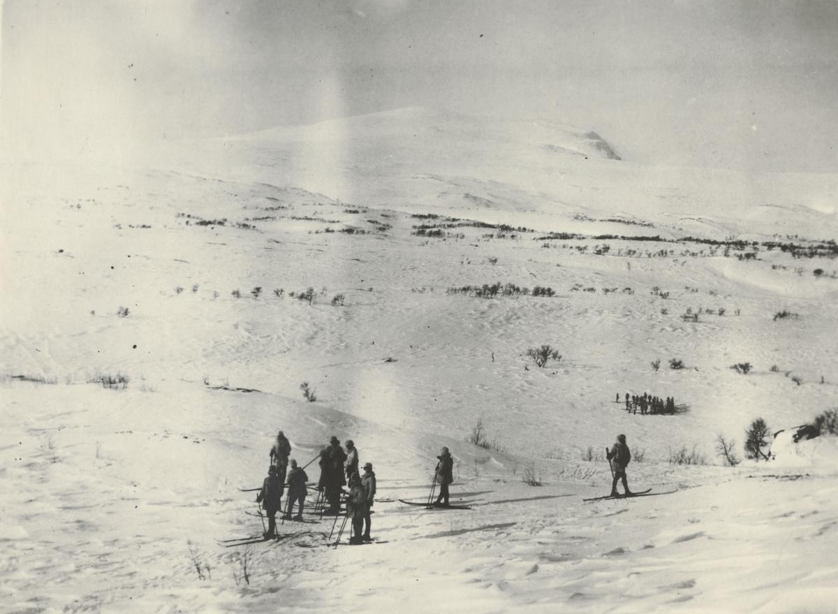 Två soldatgrupperingar på kalfjället. I bakgrunden reser sig en fjälltopp.
