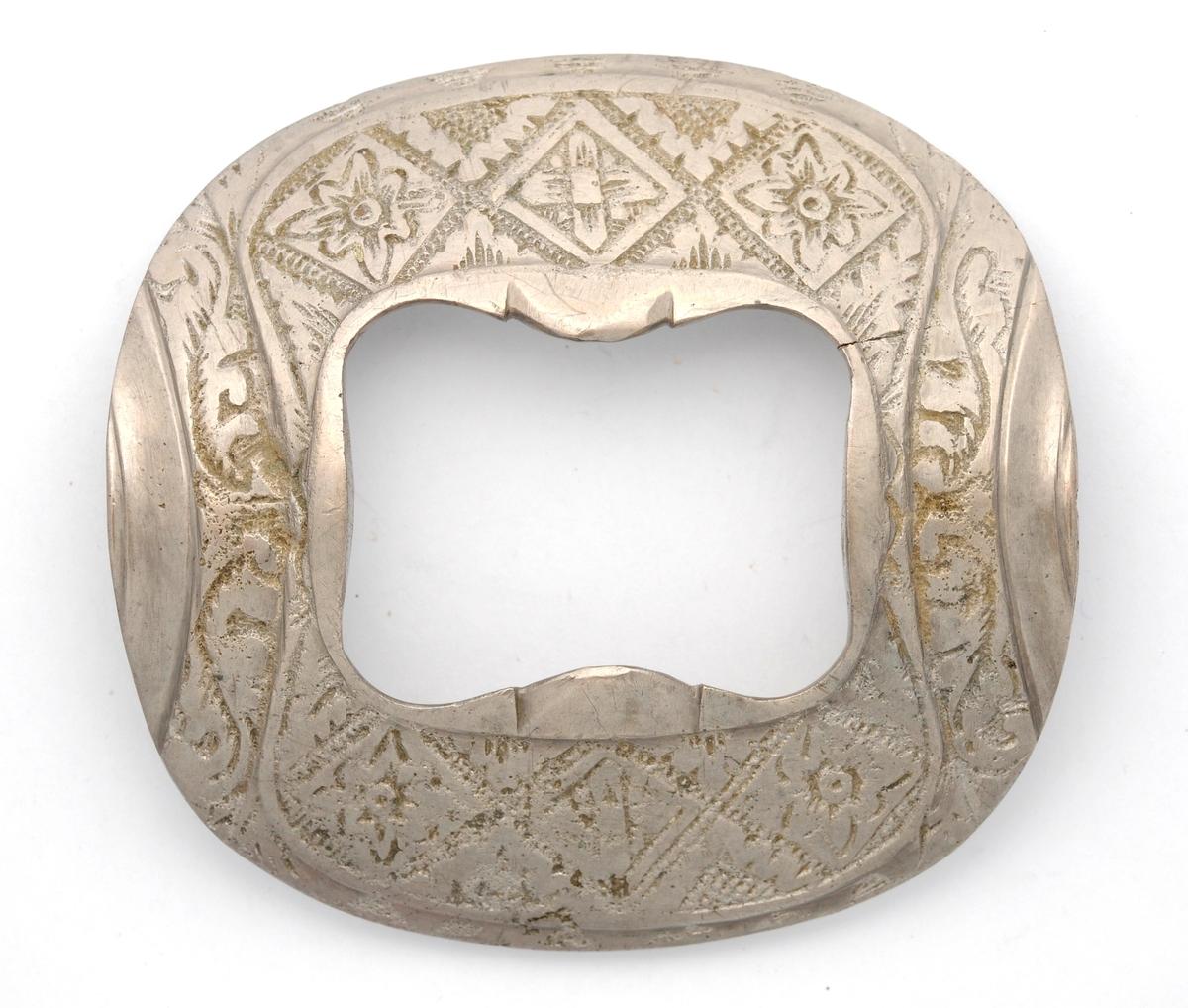 Spenne i støypt metall (tinn ?) Tilnærma rektangulær form med avrunda hjørne.  Støypt dekor. Stolpe, kalv og tann manglar.