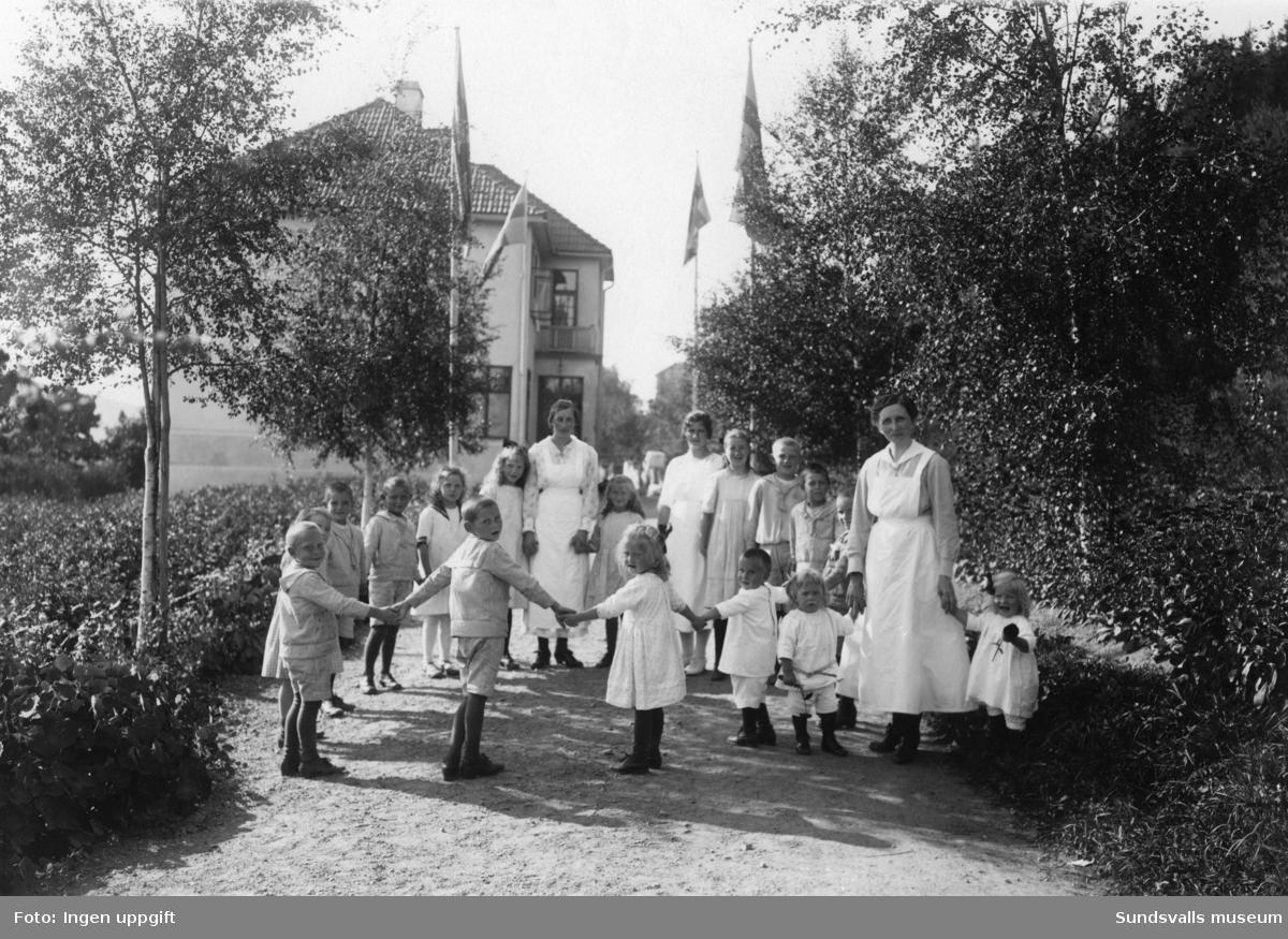 """Barn och vårdpersonal utanför Barnhemmet och Förlossningsanstalten kallat """"Vårdhem"""". Villagatan 16. Anstalten var verksam mellan 1912 till 1940 och skulle fungera som hem för nyblivna mödrar och barnupptagningsanstalt, samt intill dess ett barnbördshus fanns, även som barnbördshus. Förlossningsverksamheten upphörde dock 1935. Från 1945 fungerade anstalten som TBC-sjukstuga och döps senare om till """"Solgläntan""""."""