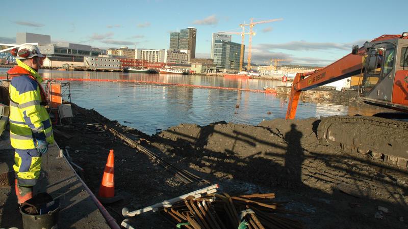 Arkeolog overvåker våtgraving på Senketunnelprosjektet. Oslo med Operaen i bakgrunnen.