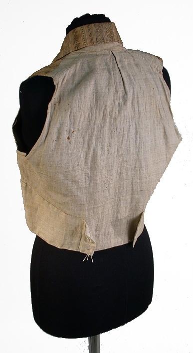 Randig i brunt och ljusbrunt med inslag av svart och vitt silke. Bakstycket av linnelärft. Dubbelknäppt. Krage med slag.