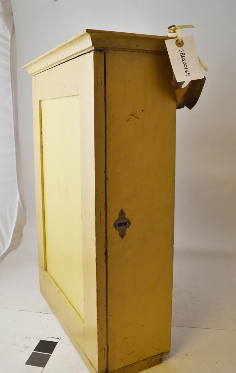 Vegghengt gult, billettskap i tre med hyller for edmonsonske billetter. Skapet kan låses, nøkkel følger med. Brukt i museumstiden på Setesdalsbanen. Kommer trolig opprinnelig fra en nedlagt stasjon langs Sørlandsbanen.