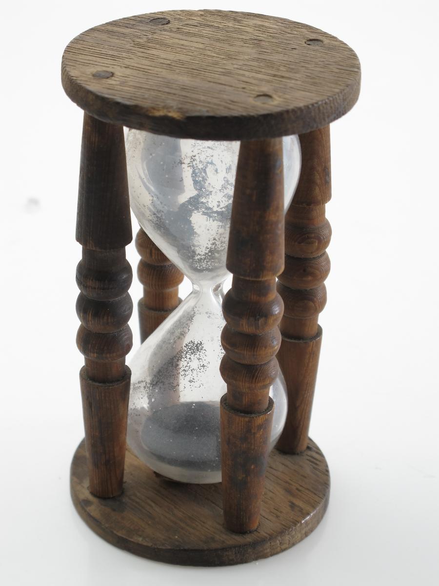 Timeglass  (10g glass), 15 sekunders. Stativ med fire dreide furu ledd,  to runde plater av eik, blågrå sand i glasset.