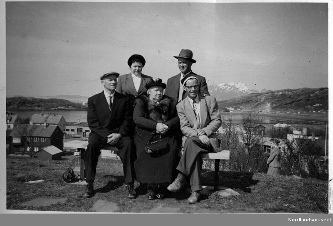 Portrett. Et eldre ektepar og en mann sitter ute på en benk. Ei dame og en mann står bak. Det eldre paret finner vi også på GBS.F.010020-00114.