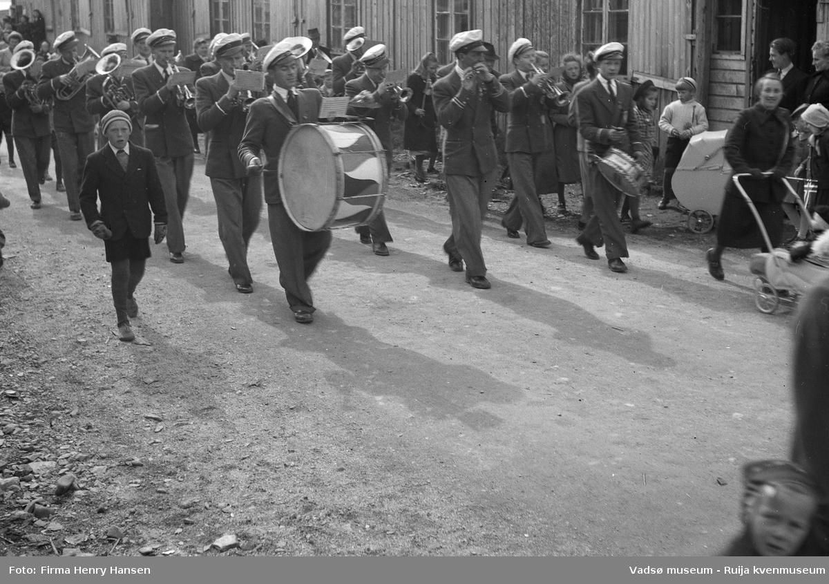 Vadsø sentrum 17. mai 1951. Musikkorps spiller i gatene.  Trommeslagerne går fremst. Musikerne har uniformer og hvite hatter. Det står tilskuere ved husveggene og to barnevogner vises. Det er muligens brakker i bakgrunnen.