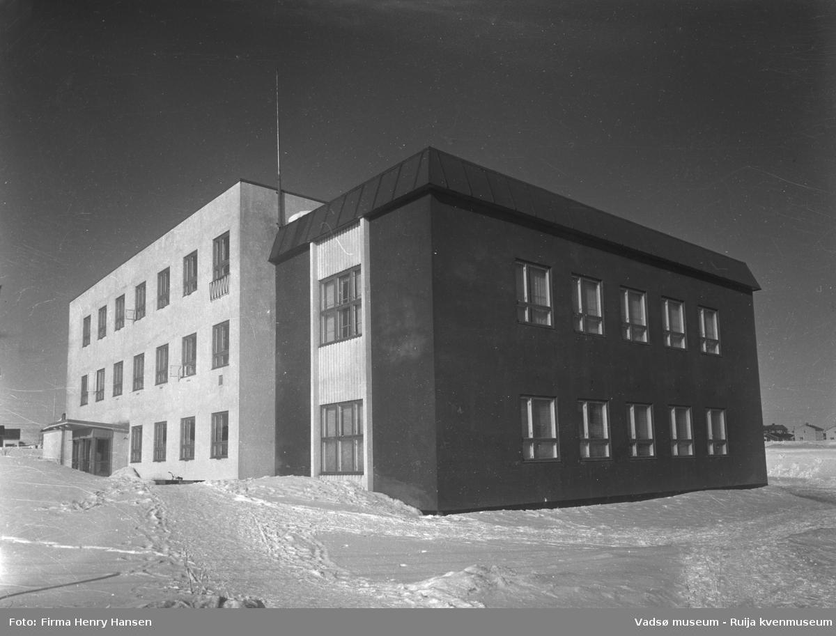 Vadsø samfunnshus. Bilder er tatt en vinterdag mot nordøst. På vestsiden av bygningen ser vi inngangspartiet. Vadsø samfunnshus' første byggetrinn var i 1957, og holdt i to og tre etasjer, bl.a. med svømmehall, kombinert fest- og gymsal, kafe og kino.