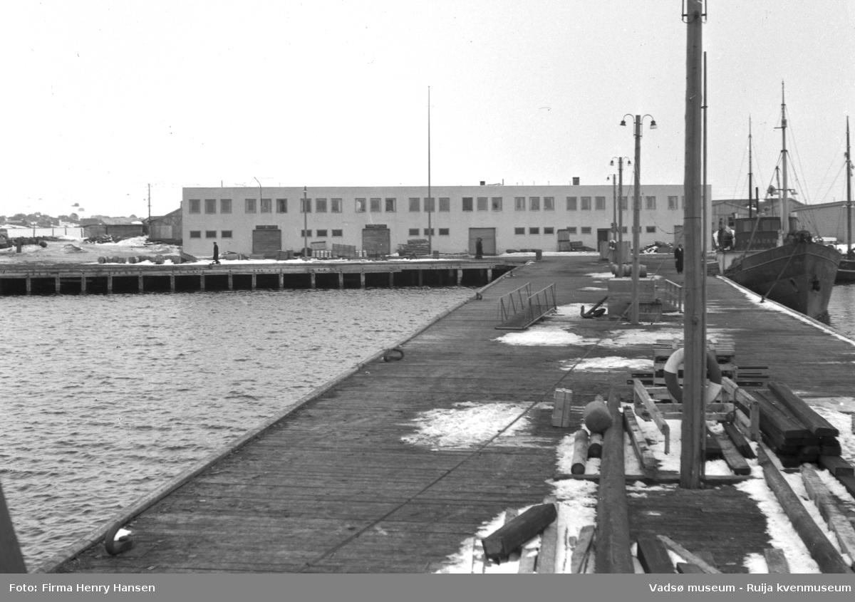 Vadsø våren 1952. Bildet er tatt ytterst fra piren til dampskispkaia fra vest mot øst. I forkant av bildet ser vi piren med blant annet lysstolper, et anker, paller, plankestabler, redningsbøyer og landgangsrampen til hurtigruta. I høyre billedkant ligger lokalbåten Haukøy som gikk i rute på Varangeren for Finnmark Fylkesrederi. I bakkkant Vadsø Havneterminal.